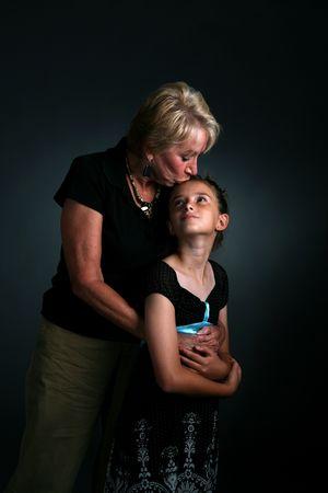 grandmother kissing granddaughter on forehead