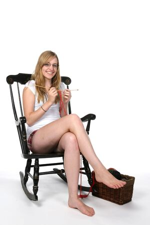 pretty young woman in rocking chair knitting photo