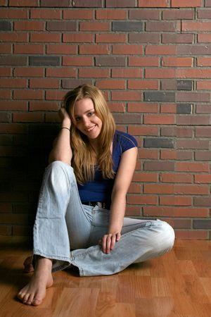 gelukkige vrouw zittend op verdieping met knie-up