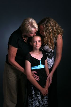 three generations of women with child being kissed Banco de Imagens