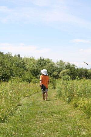 back view of young boy on walking trail carrying his sandals photo