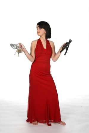teenage girl in red gown holding up two shoes as if trying to decide which pair to wear