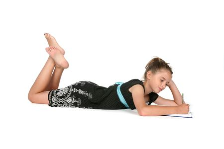 lay: girl on her belly writing on journal