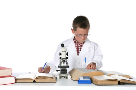 young boy in lab coat consulting text books and taking notes next to his microscope