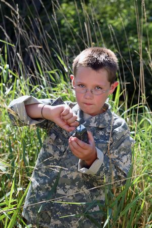 young boy in cammoflage pulling the pin on a grenade