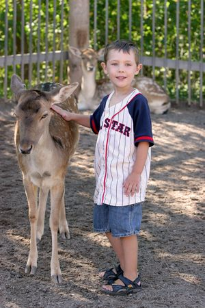 young boy touching the back of a small deer