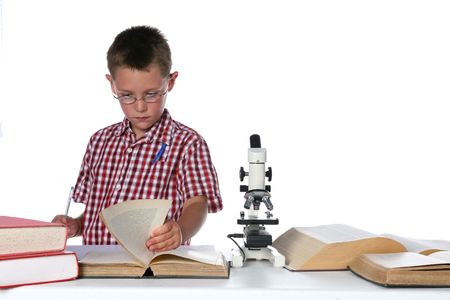 child scientist consulting a book, microscope on table and pen in his pocket