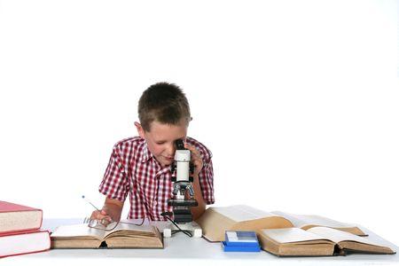 顕微鏡とノートを見てかわいい少年 写真素材