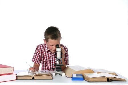 cute young boy looking through a microscope and taking notes