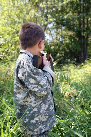 sighting: young boy sighting in a toy rifle outside