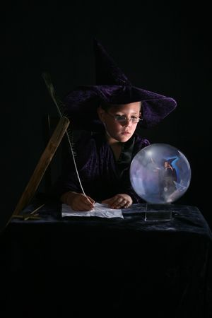 child in wizard costume writing a spell and gazing into crystal ball Zdjęcie Seryjne