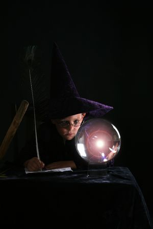 crystal gazing: child in purple wizard costume with feather pen gazing into crystal ball