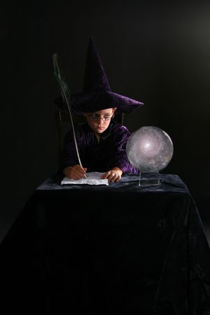 wizard boy looking into crystal ball and writing with a feather pen photo