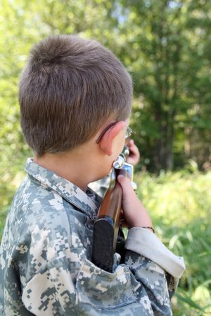 point and shoot: child in camoflauge sighting down a toy gun at the edge of a field
