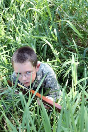 camoflauge: child in glasses and camoflauge in grass with toy gun