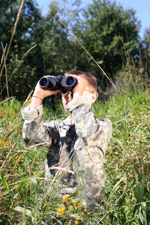 camoflauge: young boy in field, in camofllage, looking up through binoculars