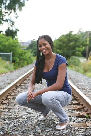 prety: prety black teenage girl crouching on train tracks