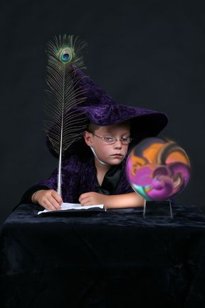 wizard child with peacock feather pen looking into colorful crysal ball photo