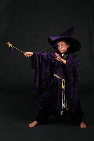 紫色のベルベットの帽子とローブの杖を保持し、呪文をウィザードの少年