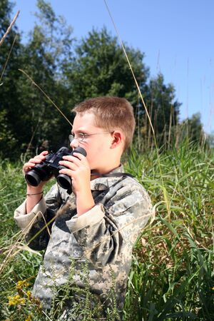 fatigues: child in camouflage holding binoculars and standing in the tall grass