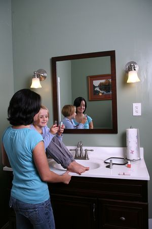 primp: young girl sitting on a vanity while older sister or babysitter helps her select cosmetics; reflected in mirror
