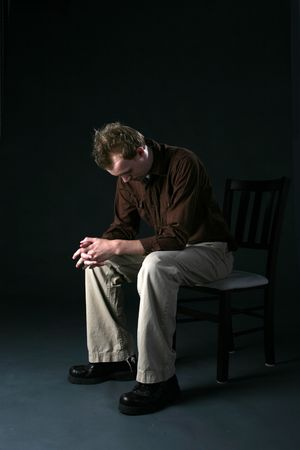 head down: solitary man sitting on chair with head down as if sad or depressed Stock Photo