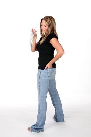 tight jeans: sexy femme qui porte des jeans serr�s et la tenue d'un collier de perles � son doigt