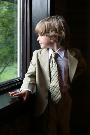 natural light portrait of cute young boy in a suit looking out a large window