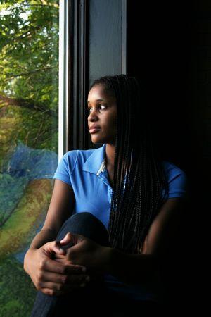 美しい黒 10 代の少女に彼女の膝と考え込むように探してウィンドウに反映されます。 写真素材
