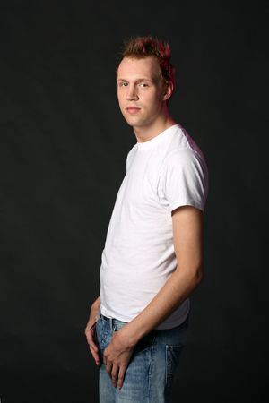 spiked hair: attractive young man in white shirt and jeans with hair spiked