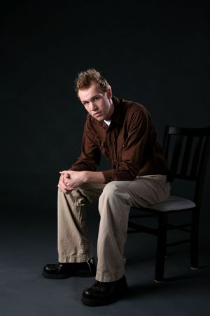 young man sitting thoughtfully on chair with his arms resting on his knees Stock Photo - 3752223