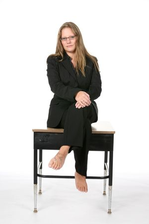 business woman in black suit and bare feet on school desk Stock Photo