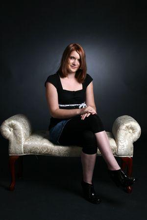 pretty auburn haired teenage girl sitting on white bench photo