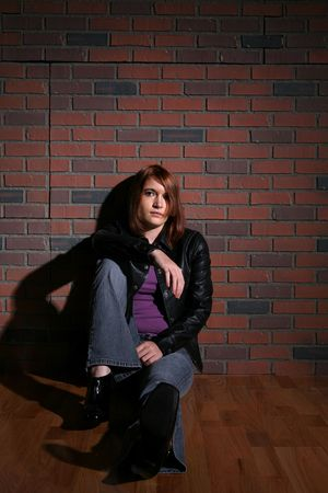 auburn hair: grunge style teen with auburn hair sitting in front of brick wall