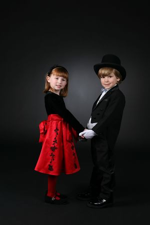 young children in formal clothing holding hands and looking at the camera photo