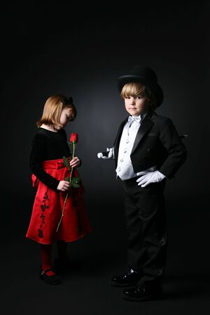 young boy in black tuxedo in foreground while girl in red dress looks at rose photo