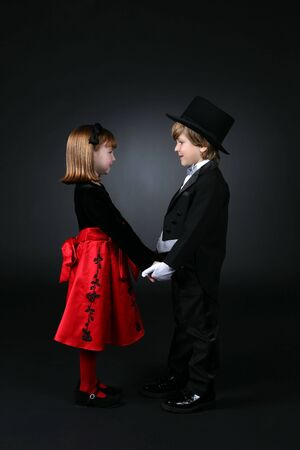 young boy in tuxedo and girl in red dress holding hands and looking at each other photo
