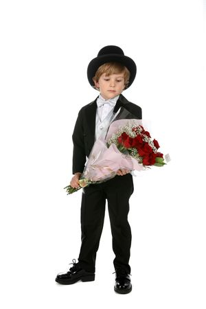 cute young boy in black tuxedo and top hat holding a bouquet of red roses Stock Photo