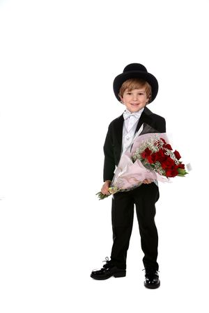 cute boy in black tuxedo holding bouquet of red roses for valentine's day or mother's day