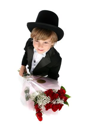 looking down at a cute boy in a tuxedo holding red roses for valentines day or mothers day photo