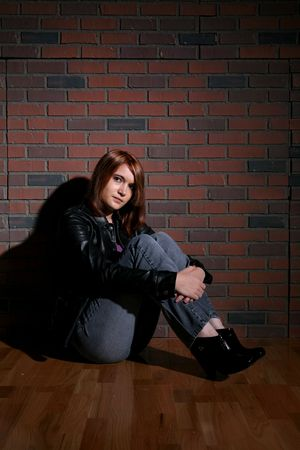 knees up: bored looking teenage girl sitting against brick background with knees up