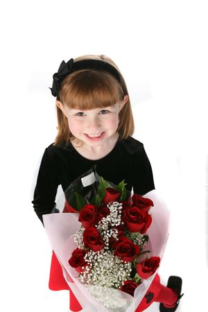 cute little girl in holiday dress holding bouquet of red roses photo