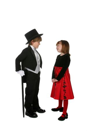 cute young boy in black tuxedo and girl in red holiday dress photo