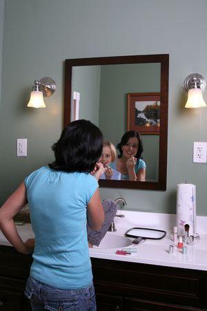 primp: ragazza guarda come anziani teen applys trucco nello specchio Archivio Fotografico