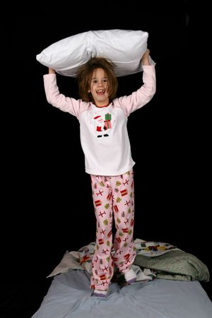 cute young girl with pillow on her head and jumping on the bed photo