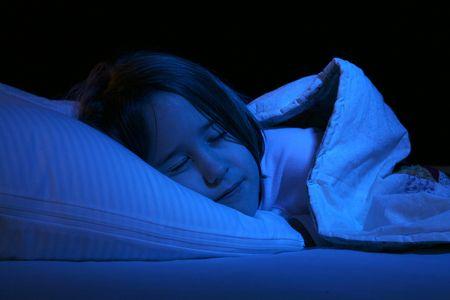 枕と毛布の下で眠っている女の子のクローズ アップ 写真素材