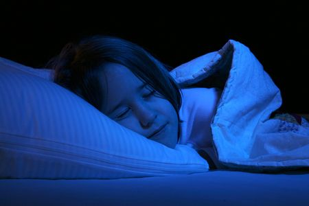 close up of girl sleeping on pillow and under a blanket Stock Photo