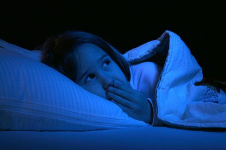 cute girl with her eyes open and hand over mouth in bed