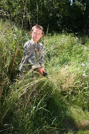 sword act: boy in American Army camoflauge hiding in the grass and scowling
