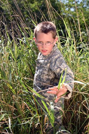camoflauge: young boy in camoflauge hiding in the tall grass Stock Photo
